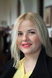 Arbeiten Sie blonde Frau im schwarzen Mantel, unscharfer Hintergrund um Stockbilder