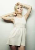 Arbeiten Sie blonde Frau im weißen Kleid um, das im Studio aufwirft Stockfoto