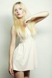 Arbeiten Sie blonde Frau im weißen Kleid um, das im Studio aufwirft Lizenzfreies Stockbild