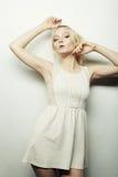Arbeiten Sie blonde Frau im weißen Kleid um, das im Studio aufwirft Lizenzfreie Stockfotografie