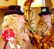Arbeiten Sie blonde Frau mit Hut im barocken Spiegel um Stockfotografie