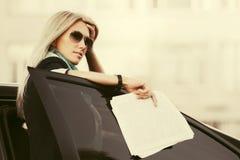 Arbeiten Sie blonde Geschäftsfrau in der Sonnenbrille durch ihr Auto um Lizenzfreie Stockfotos