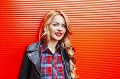 Arbeiten Sie blonde lächelnde Frau des Porträts die recht um, die schwarze Felsenart über buntem Rot trägt Stockfoto