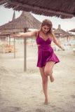 Arbeiten Sie blondes glückliches an der Seeaufstellung um, die auf Sand Schuh-los ist Lizenzfreie Stockfotografie