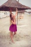 Arbeiten Sie blondes glückliches an der Seeaufstellung um, die auf Sand Schuh-los ist Lizenzfreies Stockbild