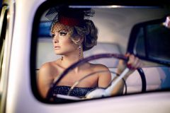 Arbeiten Sie blondes Modell im Retrostil im alten Auto um Stockbild