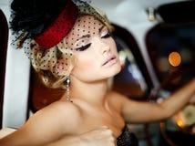 Arbeiten Sie blondes Modell im Retrostil im alten Auto um Lizenzfreies Stockbild