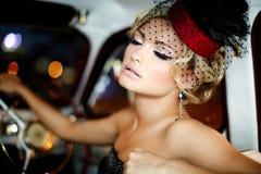 Arbeiten Sie blondes Modell im Retrostil im alten Auto um Stockfotografie