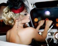 Arbeiten Sie blondes Modell im Retrostil im alten Auto um Stockbilder