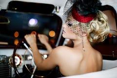 Arbeiten Sie blondes Modell im Retrostil im alten Auto um Lizenzfreies Stockfoto