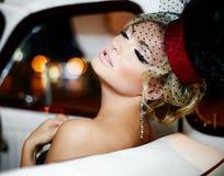 Arbeiten Sie blondes Modell im Retrostil im alten Auto um Lizenzfreie Stockfotos