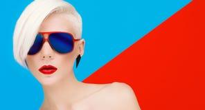 Arbeiten Sie blondes Modell mit modischem Haarschnitt und Sonnenbrille auf hellem um Lizenzfreie Stockfotos