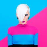 Arbeiten Sie blondes Modell mit modischer Frisur und Make-up auf einer Farbe um Stockfoto