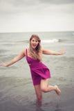 Arbeiten Sie Blondine an der Strandseeseitenaufstellung um, die im Wasser Schuh-los ist Lizenzfreie Stockbilder