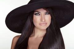 Arbeiten Sie Brunettefrau die vorbildliche Aufstellung im schwarzen Hut um, der auf whi lokalisiert wird Lizenzfreies Stockfoto