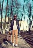 Arbeiten Sie das afrikanische Mannmodell um, das eine schwarze Lederjacke mit Tasche auf der Straße im Park trägt Stockfotografie
