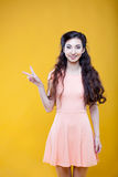 Arbeiten Sie das asiatische junge Mädchen um, das Zeichen des Sieges zeigt Stockfotos