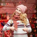 Arbeiten Sie das blonde Mädchen um, welches die stilvolle Winterkleidung trägt, die sich Daumen zeigt Stockbild