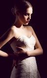 Arbeiten Sie das Foto der schönen Braut aufwerfend in der Dunkelheit um Stockfotografie