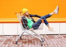 Arbeiten Sie das Frauenreiten um, das Spaß im Einkaufslaufkatzenwarenkorb hat Lizenzfreie Stockbilder