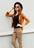 Arbeiten Sie das hübsche Frauenmodell um, das einen schwarzen Hut, Sonnenbrille und Jacke schauen im Profil über städtischem Hint Stockfoto