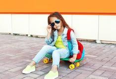 Arbeiten Sie das Kind des kleinen Mädchens um, das auf Skateboard in der Stadt über bunter Orange sitzt Stockfotos