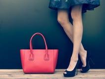 Arbeiten Sie das langbeinige Mädchen um, das in den schönen Stöckelschuhen im kurzen Jeanskleidsommer ist, der nahe der dunklen W Stockbild
