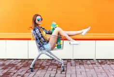 Arbeiten Sie das lächelnde kühle Mädchen um, das den Spaß hat, der im Einkaufslaufkatzenwarenkorb sitzt Lizenzfreie Stockbilder