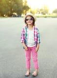 Arbeiten Sie das lächelnde Kind des kleinen Mädchens um, das ein kariertes rosa Hemd, einen Hut und eine Sonnenbrille trägt Lizenzfreie Stockbilder
