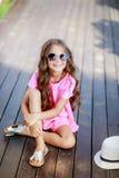 Arbeiten Sie das Modell des kleinen Mädchens um, das ein rosa kariertes Hemd, einen Hut und eine Sonnenbrille in der Stadt trägt stockfotografie