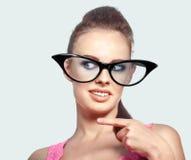 Arbeiten Sie das Porträt der lustigen Frau in den großen Gläsern um und ihre Flosse zeigen Lizenzfreie Stockfotografie