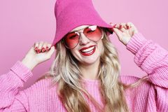 Arbeiten Sie das Porträt der modischen zufälligen jungen Frau im rosa pulover und im Hut um und über rosa Hintergrund aufwerfen S Lizenzfreies Stockfoto