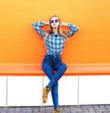 Arbeiten Sie das recht blonde Mädchen um, das über orange Hintergrund aufwirft Lizenzfreie Stockfotos