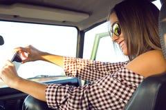 Arbeiten Sie das schöne Mädchen um, das selfie mit Smartphone im Auto nimmt Stockfotografie