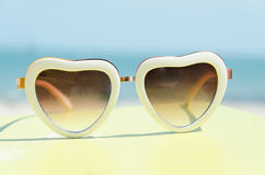 Arbeiten Sie das Sonnenbrilleherz um, das auf gelben Stand mit blauem Seehintergrund geformt wird Lizenzfreies Stockfoto