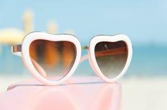 Arbeiten Sie das Sonnenbrilleherz um, das auf rosa Stand mit blauem Seehintergrund geformt wird Lizenzfreie Stockfotos