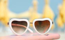 Arbeiten Sie das Sonnenbrilleherz um, das auf Strandhintergrund mit gelben Sonnenschirmen geformt wird Lizenzfreies Stockbild