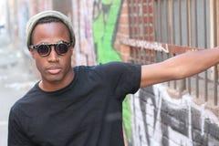 Arbeiten Sie dem afrikanischen Manntragen Sonnenbrille, Beanie, Durchdringen und schwarzes T-Stück über städtischem Hintergrund i lizenzfreies stockbild