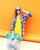 Arbeiten Sie dem recht blonden Mädchentragen Sonnenbrille mit Skateboard um Stockfoto