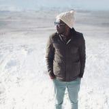 Arbeiten Sie dem stilvollen jungen afrikanischen Manntragen Sonnenbrille, Strickmütze und Jacke am Wintertag über Schnee um Stockfoto