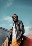 Arbeiten Sie den eleganten jungen afrikanischen Mann um, der eine schwarze Lederjacke trägt Stockbild