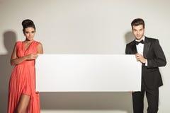 Arbeiten Sie den Mann und Frau um, die ein leeres Brett halten Lizenzfreies Stockbild