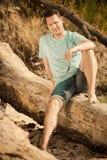 Arbeiten Sie den Porträtgutaussehenden mann um, der auf Baum durch Meer sitzt Stockfotos