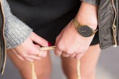 Arbeiten Sie Details, die junge Geschäftsfrau um, die ihre Tasche hält tragender goldener Schmuck und Uhr geordnet in den warmen  Stockfotografie