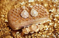 Arbeiten Sie Diamantohrringe und goldene Armbanduhr, das accessori der Frauen um Stockfoto