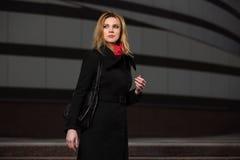 Arbeiten Sie die blonde Frau im schwarzen Mantel gehend auf Nachtstraße um Stockbilder