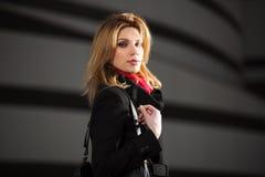 Arbeiten Sie die blonde Frau im schwarzen Mantel gehend auf Nachtstraße um Lizenzfreie Stockfotos