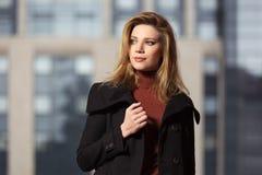 Arbeiten Sie die blonde Frau im schwarzen Mantel gehend auf Stadtstraße um Stockbild