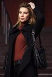 Arbeiten Sie die blonde Frau im schwarzen Mantel gehend auf Stadtstraße um Lizenzfreies Stockfoto