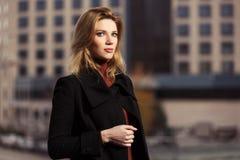 Arbeiten Sie die blonde Frau im schwarzen Mantel gehend auf Stadtstraße um Stockfotos